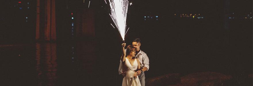 Photo de deux mariés. La mariée tient un feu d'artifice dans sa main droite.